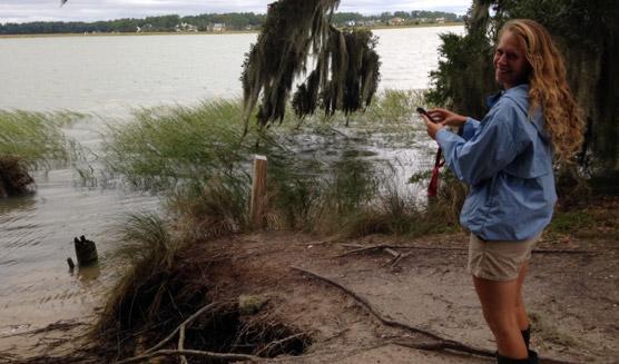 Kayla Clark uses a phone application to document the high tide on Skidaway Island.